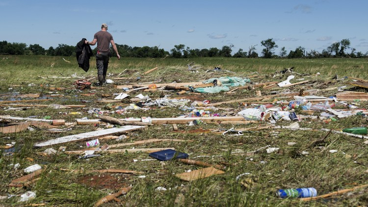 Kyle Allen walks his parents' property in Canton, Texas on Sunday, April 30, 2017, looking for personal items. Severe storms including tornadoes swept through several small towns in East Texas, killing several people, and leaving a trail of overturned vehicles, mangled trees and damaged homes, authorities said Sunday.
