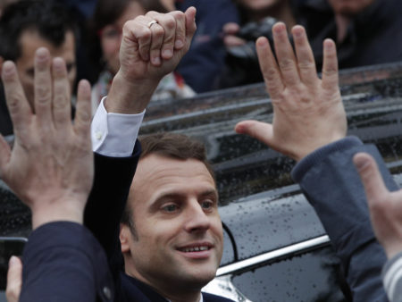 French independent centrist presidential candidate Emmanuel Macron waves as he leaves the polling station after casting his ballot in the presidential election in Le Touquet, France, Sunday. Macron was declared the winner based on early vote counts by the French Interior Ministry.