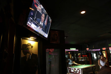 A television shows testimony by former FBI director James Comey before the Senate Intelligence Committee as patrons play pool at Mac's Club Deuce, Thursday, June 8, 2017, in Miami Beach, Fla.