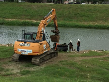 A crew from Huffman Contractors LLC works on the first day of the expansion of the program at Brays Bayou, southeast of downtown Houston.