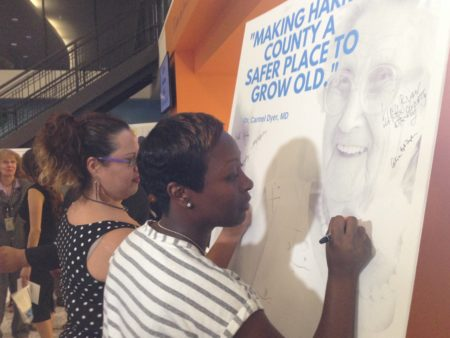 Monica Lara and Malishia Janice sign a pledge displayed after an event to officially announce the Harris County Senior Justice Assessment Center.