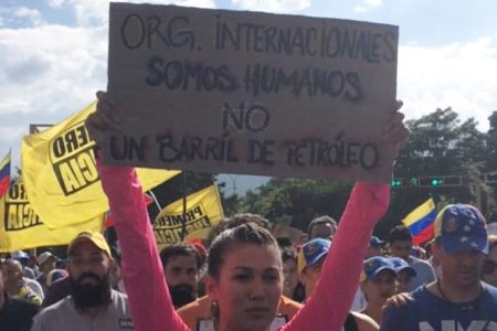 """At a protest in Venezuela, this woman's sign reads """"We are human not a barrel of oil """""""