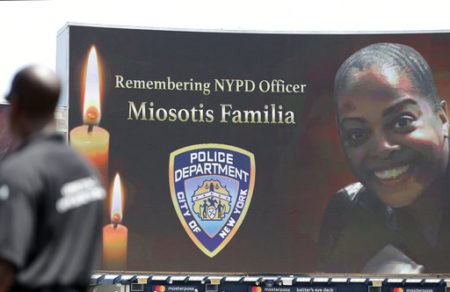 "A security guard stands at attention as New York Police Department officer Miosotis Familia is memorialized before the start of a baseball game between the New York Yankees and the Toronto Blue Jays in New York, Wednesday, July 5, 2017. Familia was killed in an ""unprovoked attack,"" in the Bronx borough of New York, according to the NYPD Commissioner."