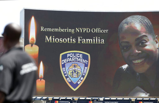 """A security guard stands at attention as New York Police Department officer Miosotis Familia is memorialized before the start of a baseball game between the New York Yankees and the Toronto Blue Jays in New York, Wednesday, July 5, 2017. Familia was killed in an """"unprovoked attack,"""" in the Bronx borough of New York, according to the NYPD Commissioner."""