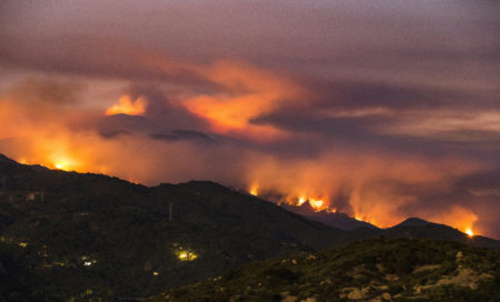 This photo provided by Eliot Oppenheimer, taken late in the evening Sunday, July 9, 2017, shows the Whittier fire burning in the mountains west of Santa Barbara, Calif. In Southern California, thousands of people remained out of their homes as a pair of fires raged at different ends of Santa Barbara County. The fires broke out amid a blistering weekend heat wave that toppled temperature records.