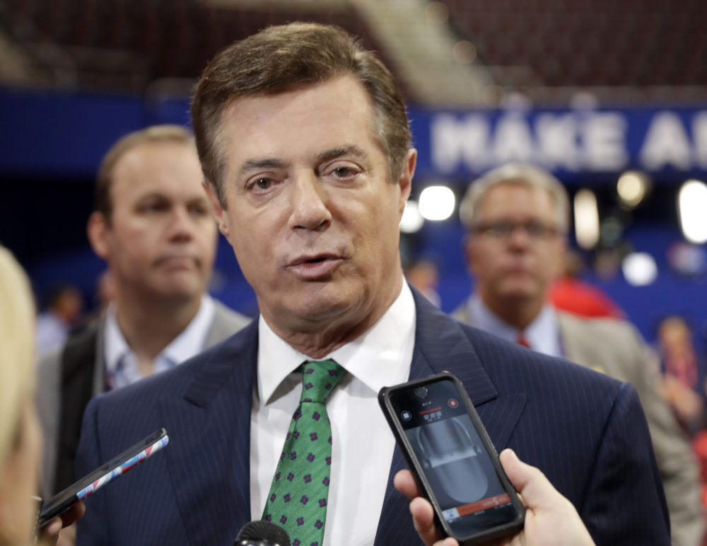 In this July 17, 2016 file photo, Trump Campaign Chairman Paul Manafort talks to reporters on the floor of the Republican National Convention at Quicken Loans Arena in Cleveland as Rick Gates listens at back left. Emails obtained by The Associated Press shed new light on the activities of a firm run by Donald Trump's campaign chairman. They show it directly orchestrated a covert Washington lobbying operation on behalf of Ukraine's ruling political party, attempting to sway American public opinion in favor of the country's pro-Russian government. Manafort and his deputy, Rick Gates, never disclosed their work as foreign agents as required under federal law.