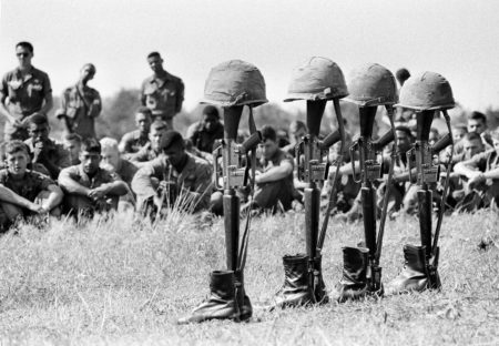 U.S. soldiers bow their heads at memorial services at Lai Khe, Vietnam, Dec. 17, 1965, for comrades killed in action the week before. The rifles, helmets and boots belong to the seven casualties killed during a search and destroy operation in the jungle west of Lai Khe.