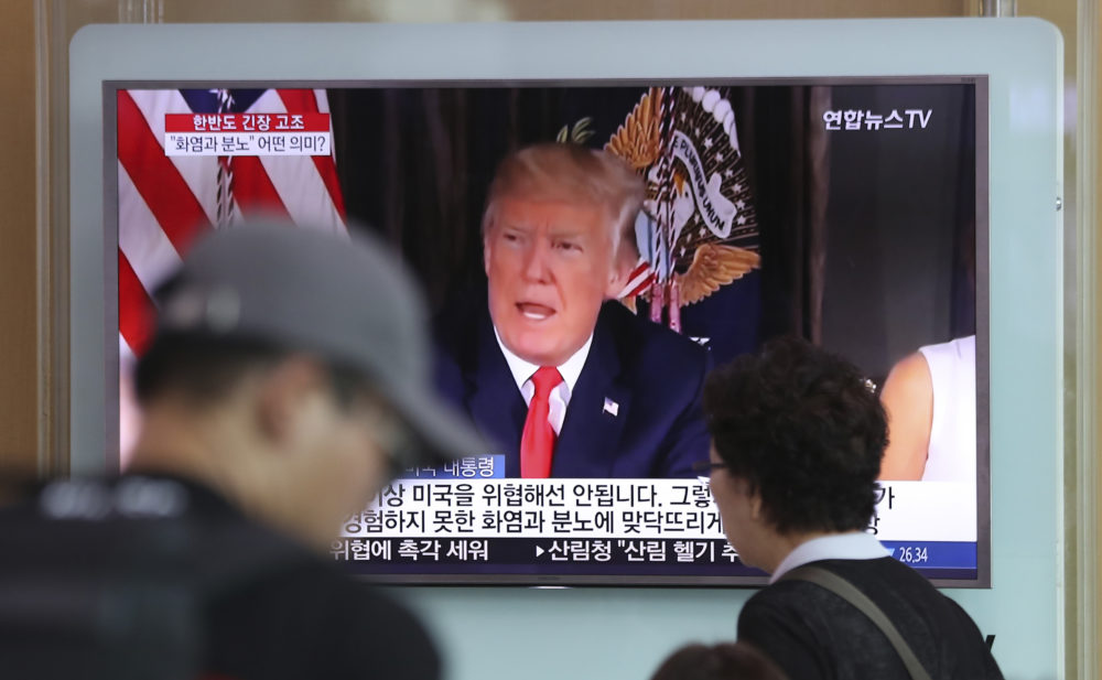 """People walk by a TV screen showing a local news program reporting with an image of U.S. President Donald Trump at the Seoul Train Station in Seoul, South Korea, Wednesday, Aug. 9, 2017. North Korea and the United States traded escalating threats, with President Donald Trump threatening Pyongyang """"with fire and fury like the world has never seen"""" and the North's military claiming Wednesday it was examining its plans for attacking Guam."""