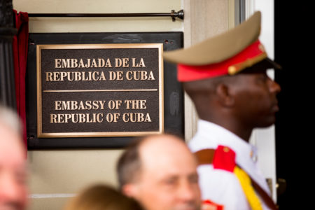 A member of the Cuban honor guard stands next to a new plaque at the front door of the newly reopened Cuban embassy in Washington, Monday, July 20, 2015. Cuba's blue, red and white-starred flag was hoisted Monday at the country's embassy in Washington in a symbolic move signaling the start of a new post-Cold War era in U.S.-Cuba relations.