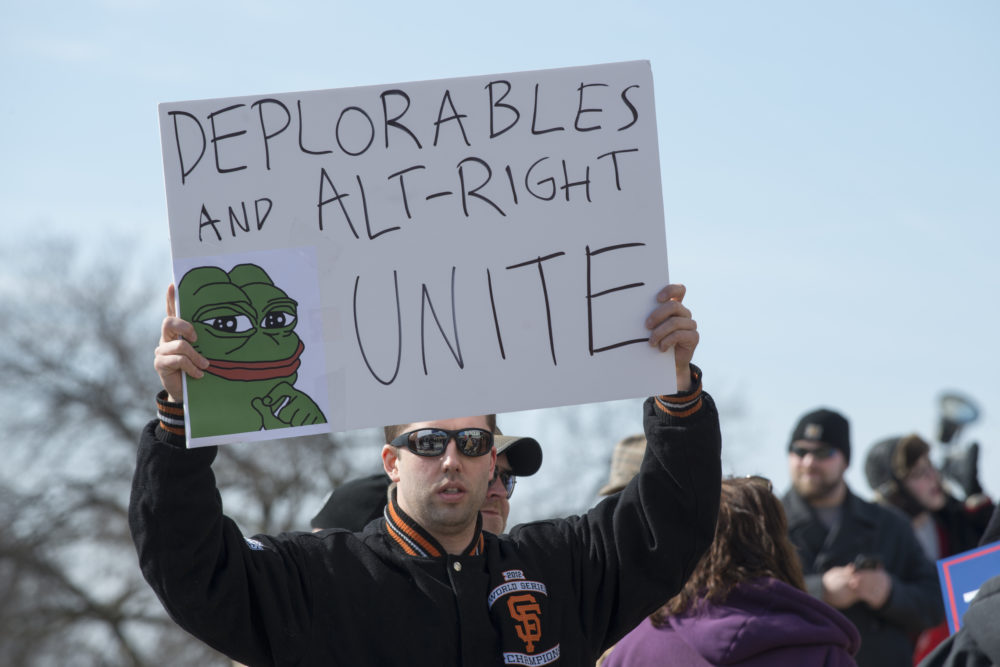 """A Trump supporter holding up a sign reading """"Deplorables and Alt-Right Unite,"""" including an image of Pepe the Frog. The cartoon character has become a symbol for white supremacist groups."""