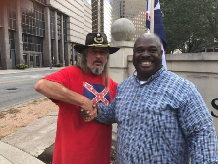 "Counter-protester Vince Powers (L) and rally participant, Douglas Earl Brown (R) share a moment of comradery before the start of the ""Destroy the Confederacy"" rally."
