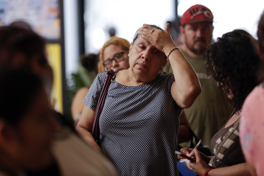 A woman waits with others in line for donated goods from a makeshift distribution center set up among the cubicles of an office Friday, Sept. 1, 2017,, in Pasadena, Texas. Thousands of people have been displaced by torrential rains and catastrophic flooding since Harvey slammed into Southeast Texas last Friday.