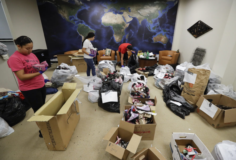 Volunteers sort donated items in a makeshift distribution center set up among the cubicles of an office Friday, Sept. 1, 2017, in Pasadena, Texas. Thousands of people have been displaced by torrential rains and catastrophic flooding since Harvey slammed into Southeast Texas last Friday.