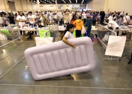 A girl carries an air mattress at a shelter setup inside NRG Center for flood victims of Harvey Wednesday, Aug. 30, 2017, in Houston. (AP Photo/David J. Phillip)