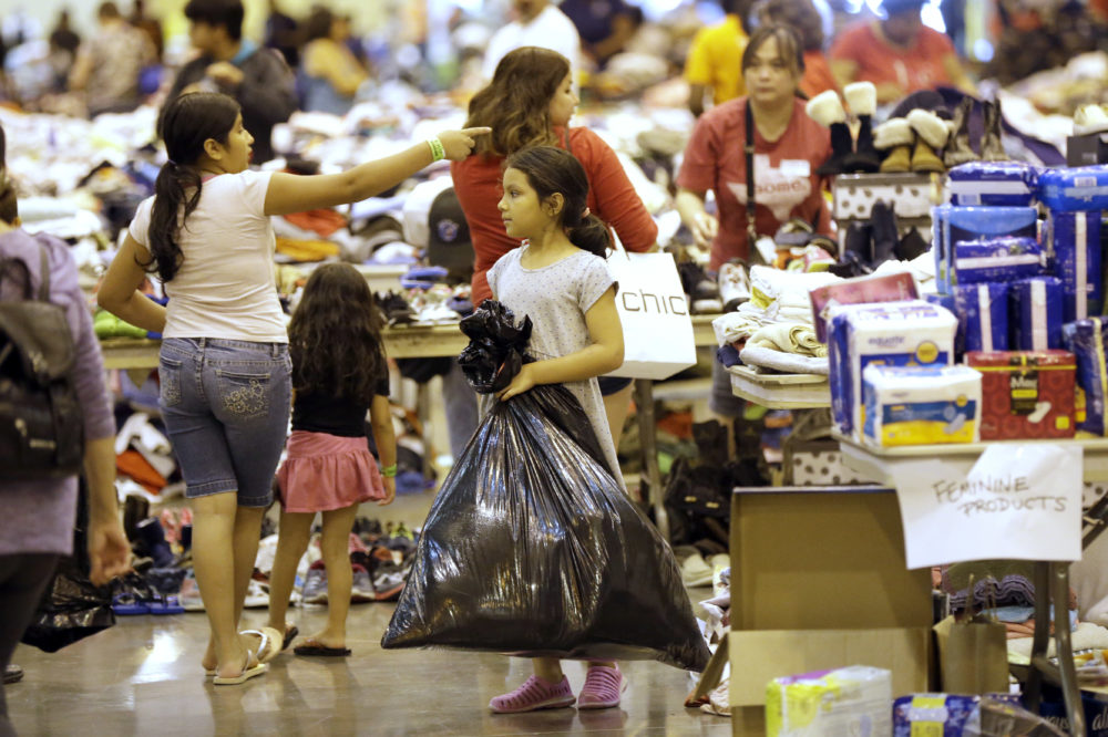 A Harvey flood evacuated child carries donated supplies in a trash bag at a shelter setup inside NRG Center, Wednesday, Aug. 30, 2017, in Houston. (AP Photo/David J. Phillip)