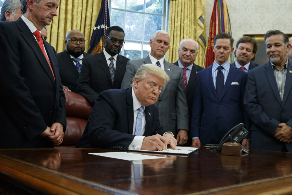 Faith leaders look on as President Donald Trump signs a proclamation for a national day of prayer to occur on Sunday, Sept. 3, 2017, in the Oval Office of the White House, Friday, Sept. 1, 2017, in Washington.