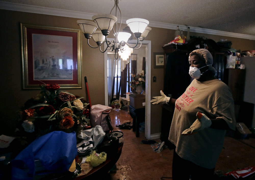 Lois Rose looks over belongings while salvaging items from her flood-damaged house Thursday, Aug. 31, 2017, in Houston. The city continues to recover from record flooding caused by Hurricane Harvey.