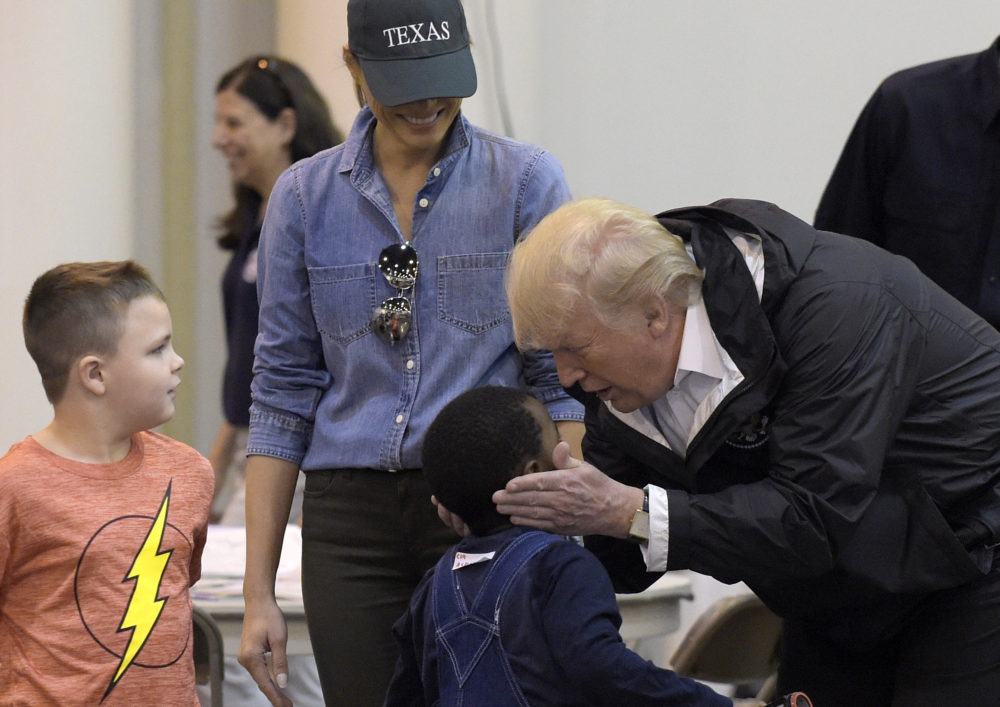 President Donald Trump and Melania Trump meet people impacted by Hurricane Harvey during a visit to the NRG Center in Houston, Saturday, Sept. 2, 2017. Trump cupped a boy's face in his hands and then gave him a high-five. It was his second trip to Texas in a week, and this time his first order of business was to meet with those affected by the record-setting rainfall and flooding. He's also set to survey some of the damage and head to Lake Charles, Louisiana, another hard-hit area.