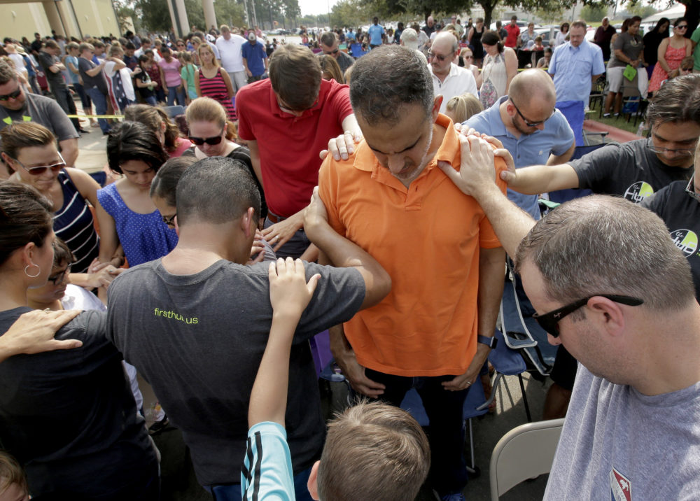 Church members gather to pray around flood victim Carlos Ochoa during Sunday service in the parking lot of the First Baptist Church Sunday, Sept. 3, 2017, in Humble, Texas. The church building was flooded with two feet of water from Hurricane Harvey prompting services to be held in the parking lot for about 2,000 people.