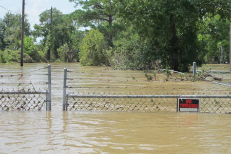 In this Aug. 31, 2017 file photo, a barbed-wire fence encircles the Highlands Acid Pit that was flooded by water from the nearby San Jacinto River as a result from Harvey in Highlands, Texas. Floodwaters have inundated at least five highly contaminated toxic waste sites near Houston, raising concerns that the pollution there might spread.
