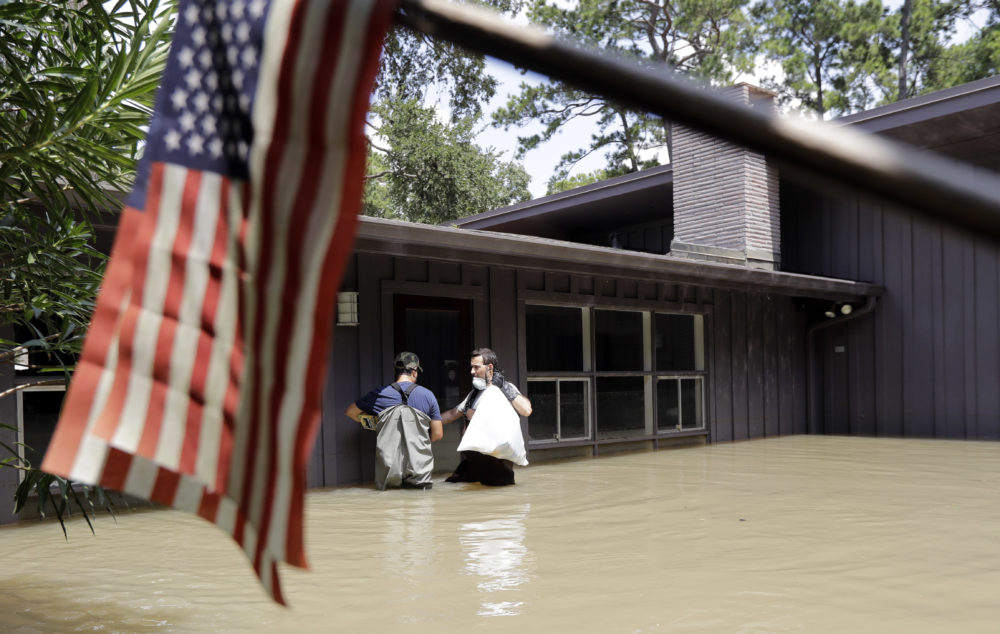 Gaston Kirby, right, and Juan Minutella leave Kirby's flooded home in the aftermath of Hurricane Harvey, Monday, Sept. 4, 2017, near the Addicks and Barker Reservoirs, in Houston.