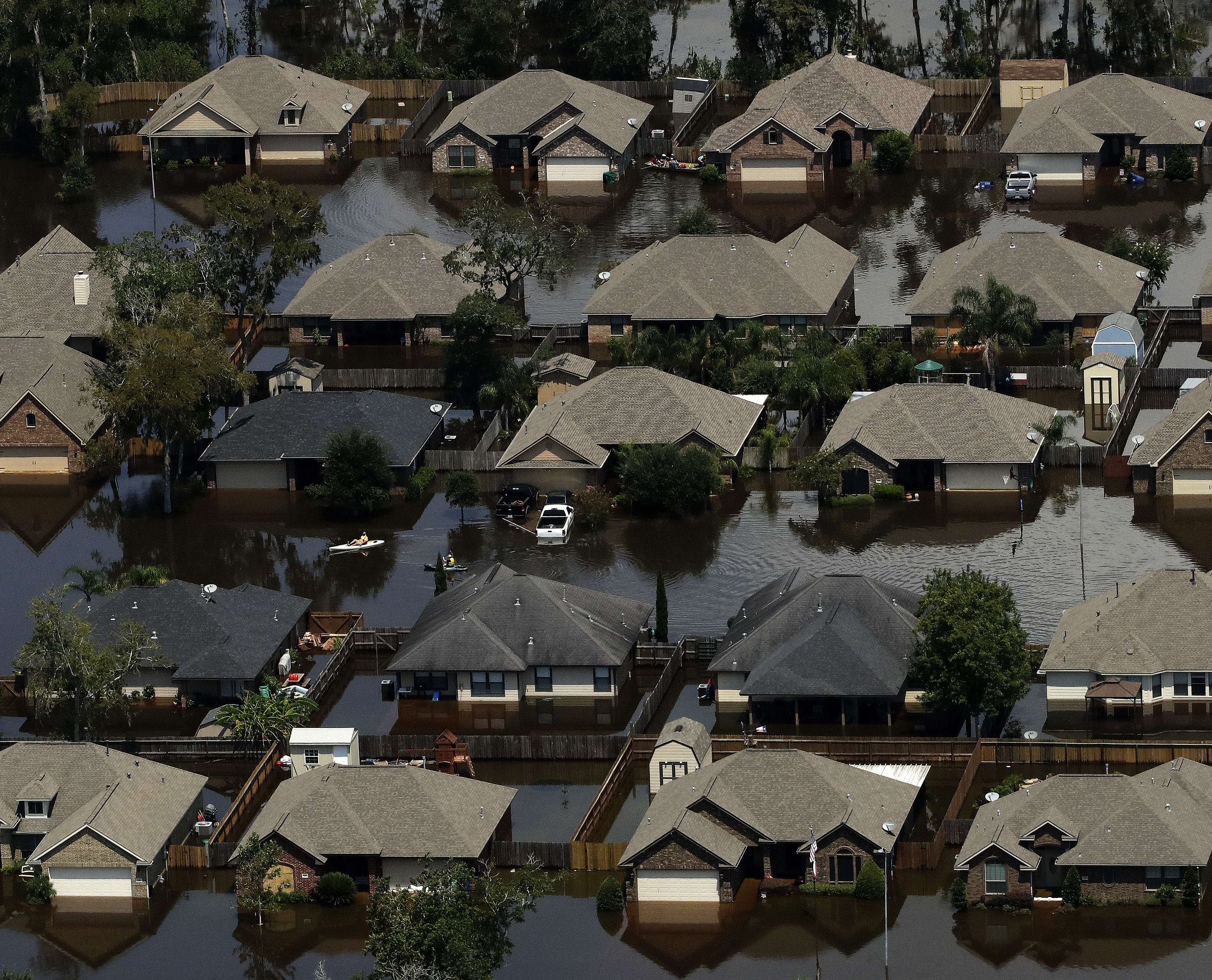 Homes are surrounded by water from the flooded Brazos River in the aftermath of Hurricane Harvey Friday, Sept. 1, 2017, in Freeport, Texas.