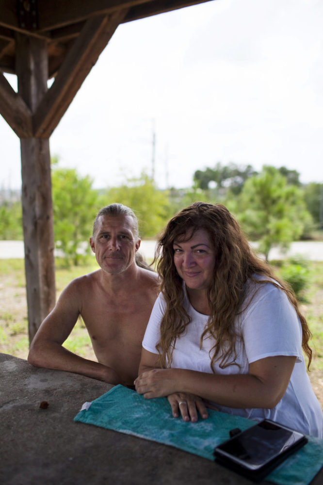 Erik Ryan and Mia Reynolds from San Leon, Texas, wait on hold with FEMA at their campsite at Bastrop State Park in Texas on Sunday. Running out of money and resources, they were relieved to hear Texas Gov. Greg Abbott's announcement that Texas State Parks were open for the month of September for evacuees, free of charge.