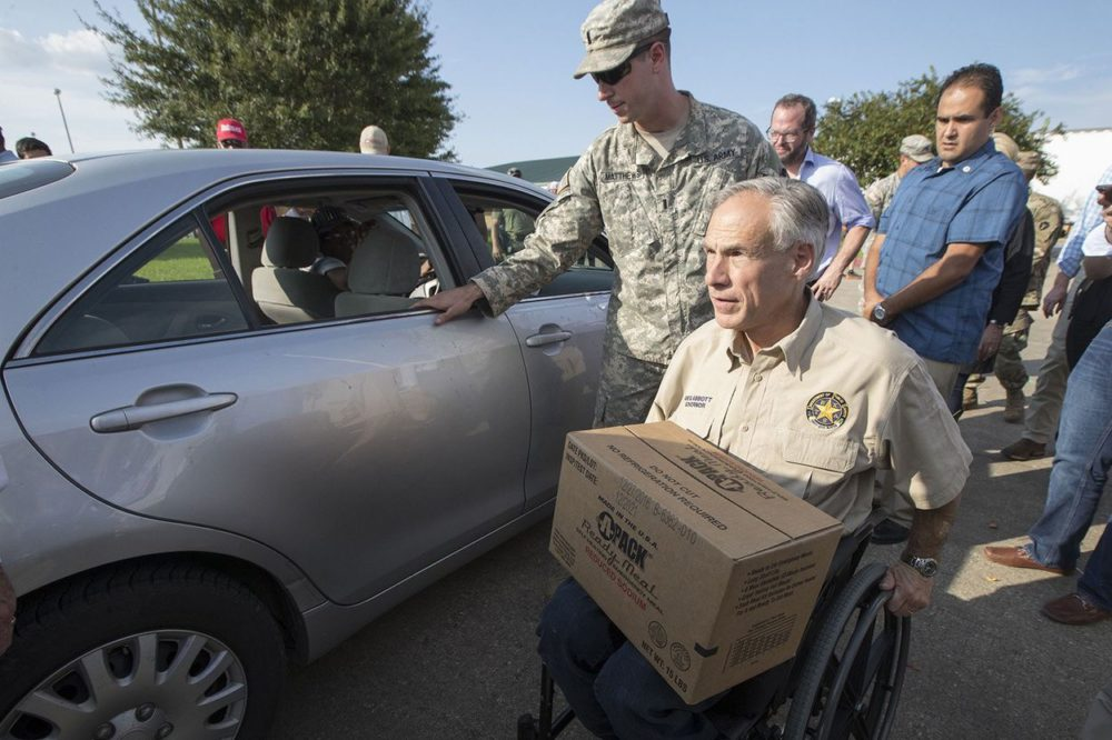 Gov. Greg Abbott hands out food at an aid distribution center in Beaumont on Tuesday, Sept. 5, 2017.