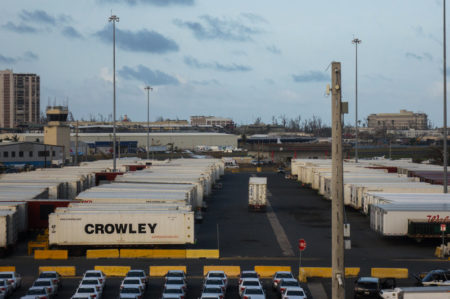 Crowley shipping containers with running refrigeration systems are lined up at in the port of San Juan, Puerto Rico. They've been there for days, goods locked away inside.