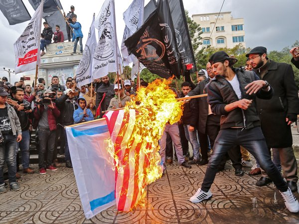 Palestinian protesters burn U.S. and Israeli flags in Gaza City on Wednesday. President Trump is set to recognize Jerusalem as Israel's capital, upending decades of U.S. policy and ignoring dire warnings from allies.