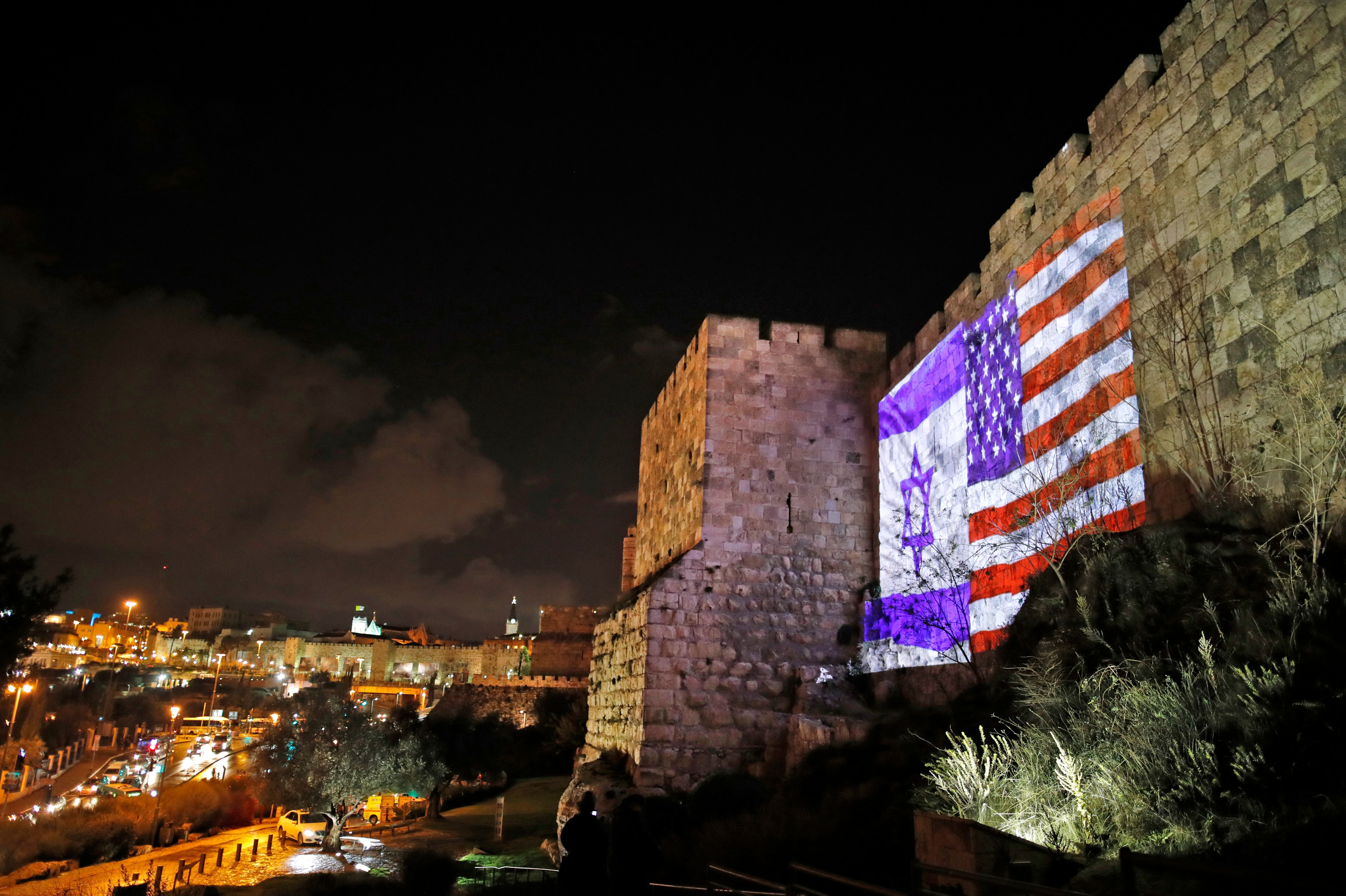 The American and Israeli flags are on display Wednesday on the walls of the Old City of Jerusalem. President Trump announced that the U.S. will view Jerusalem as the capital of Israel, and he ordered the State Department to