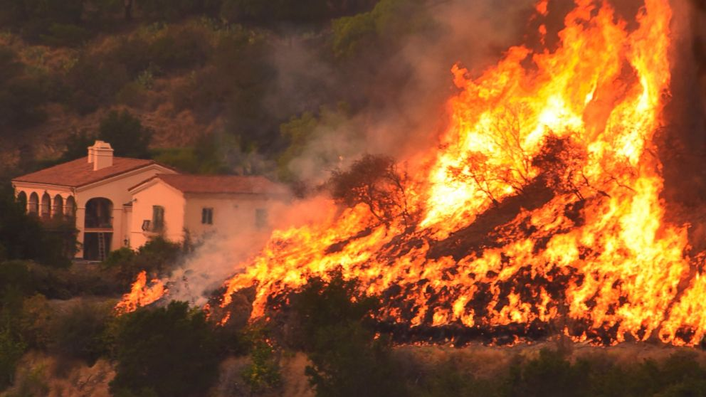In this Thursday, Dec. 14, 2017, shows flames from a back firing operation underway rise behind a home off Ladera Ln near Bella Vista Drive in Santa Barbara, Calif.