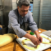 Carlos Benitez, owner of La Mexicana Bakery and Taqueria outside Washington, D.C., puts decorations on rosca de reyes before it goes into the oven. This year Benitez expects to sell almost 300 of the cakes.