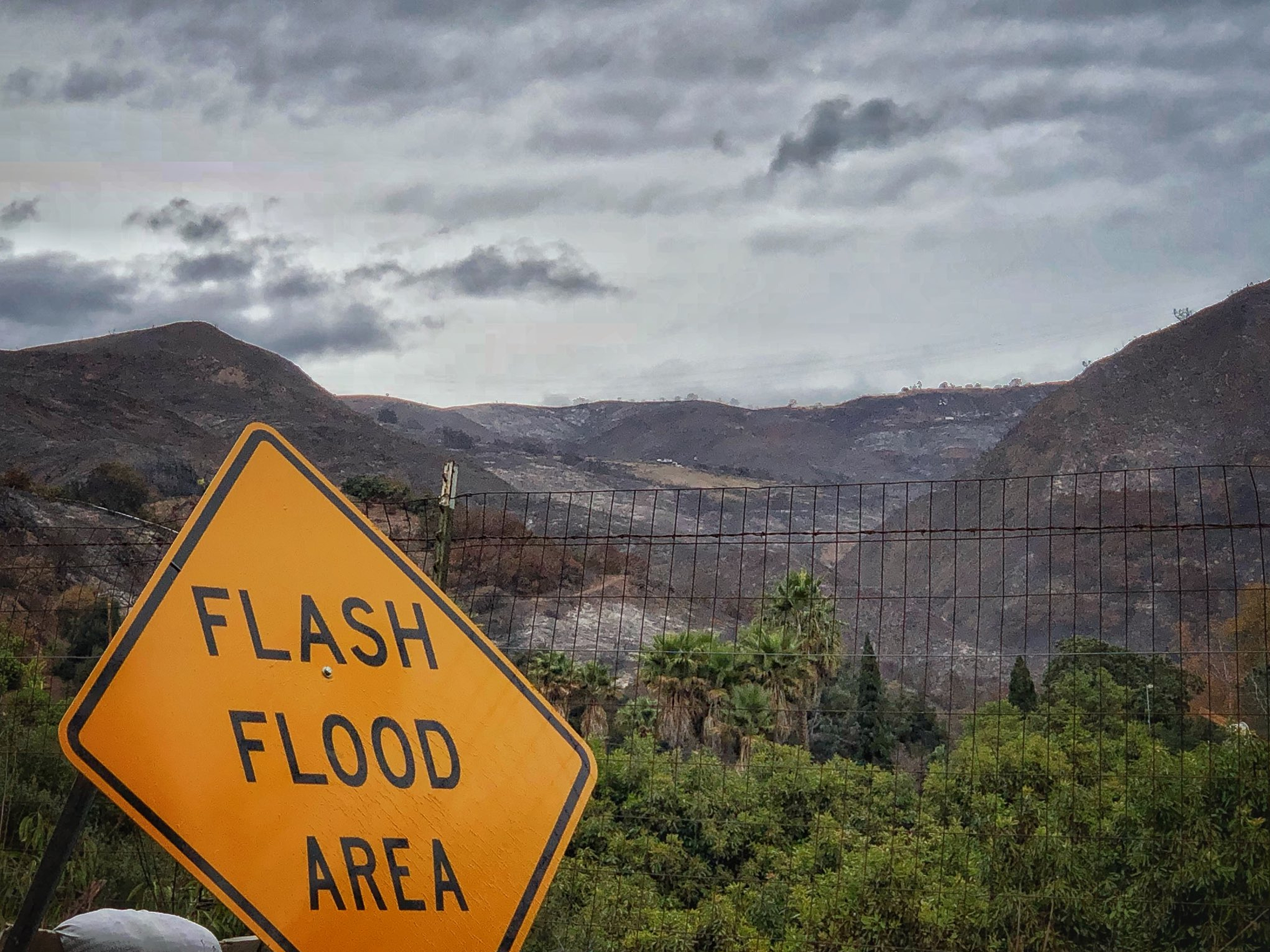 A flash flood area sign is posted as residents evacuate from several fire-ravaged communities in Santa Barbara, Calif.