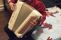 Alex, 14, plays the accordion in his bedroom. He has been learning how to play one of his dad's favorite songs, <em>La Puerta Negra</em>, or