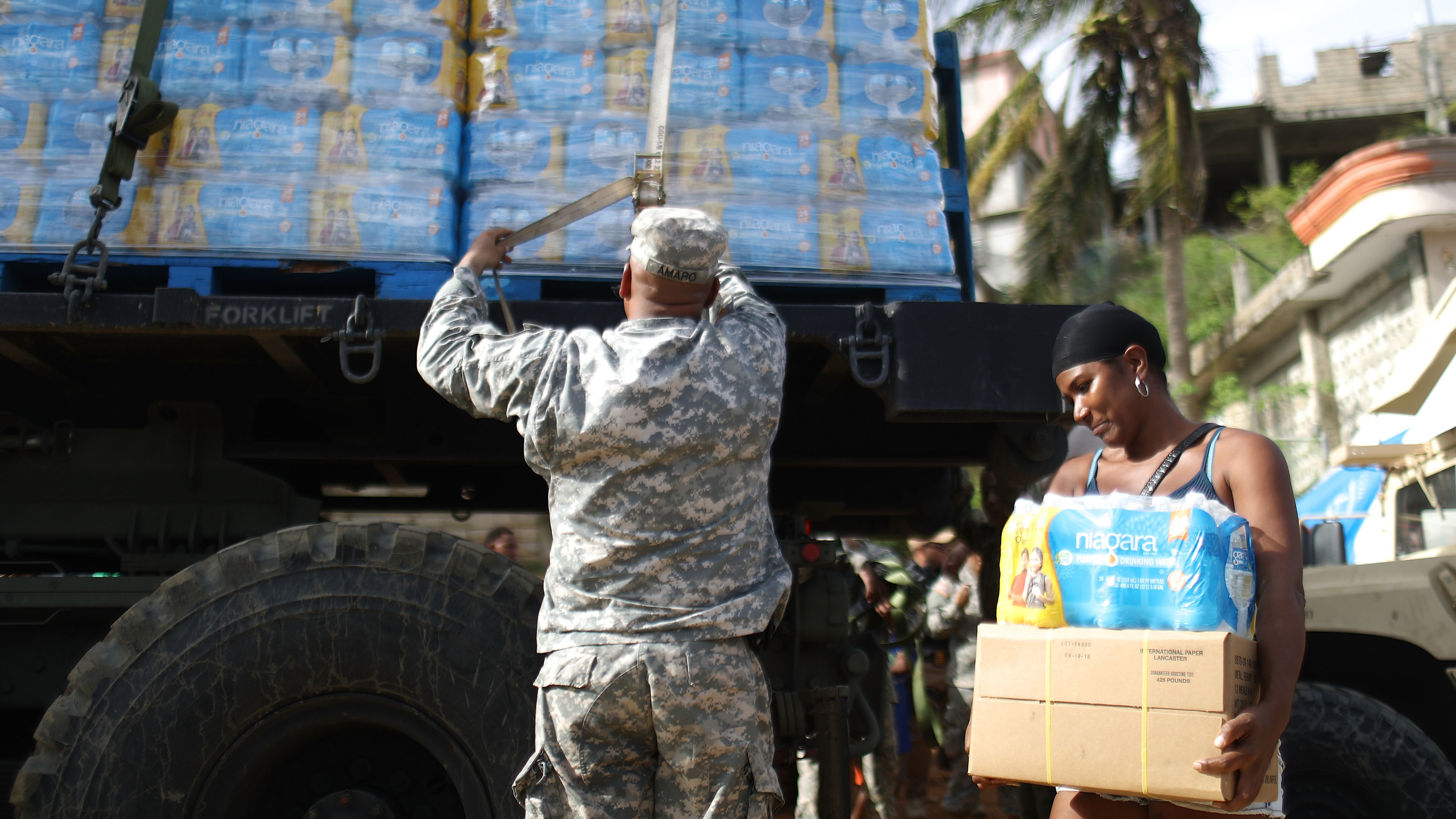 A U.S. Army soldier unloads a shipment of water provided by FEMA as a resident walks past in San Isidro, Puerto Rico