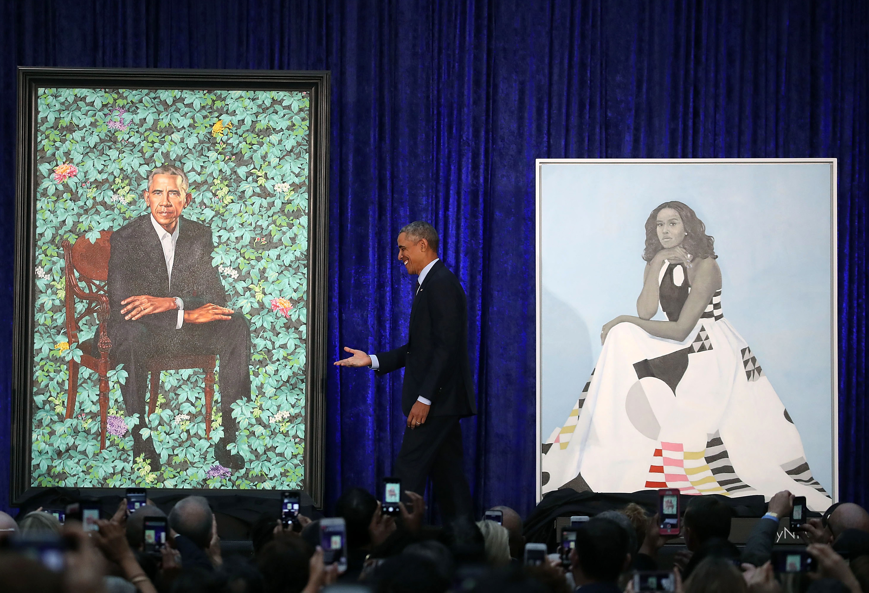 Obama stands between the portraits. His will be permanently installed in the