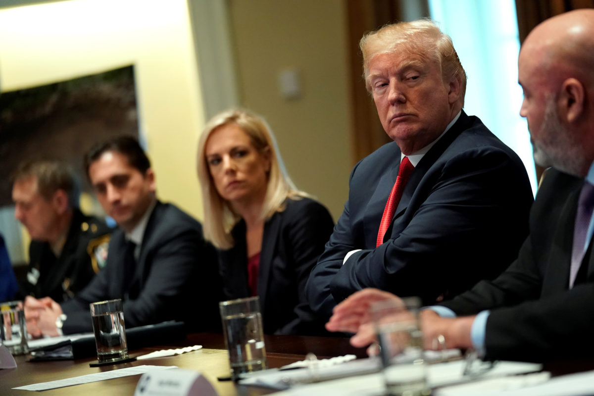 President Donald Trump, flanked by Secretary of Homeland Security Kirstjen Nielsen (C), meets with members of Congress and U.S. law enforcement about crime and immigration issues, specifically the MS-13 gang, at the White House in Washington, D.C.
