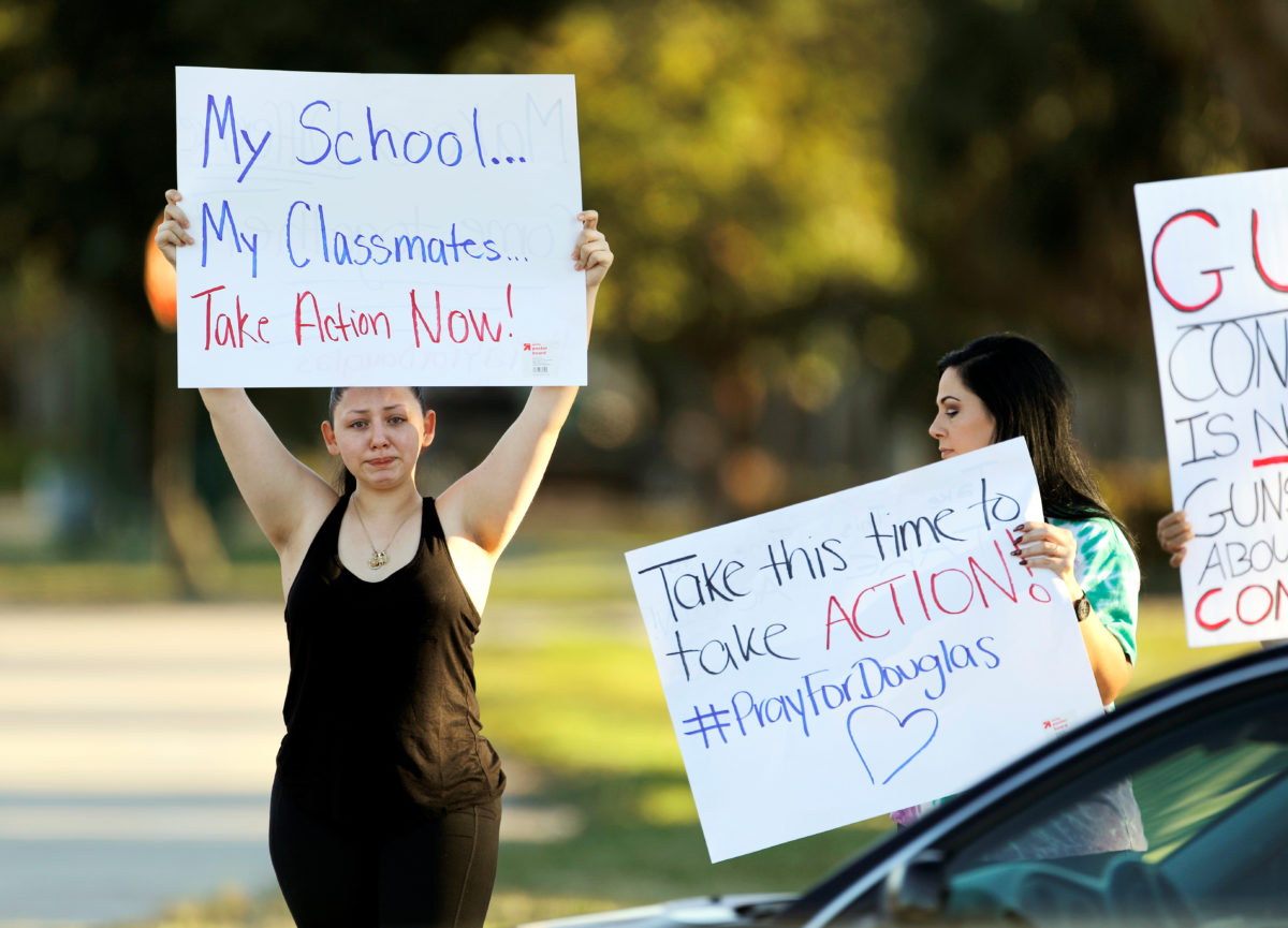Angelina Lazo (L), an 18-year-old senior at Marjory Stoneman Douglas High School, who said that she lost two friends in the shooting at her school two days ago, reacts to honks of support from passing motorists as she and her mother, Linda Lazo, right, join other gun control proponents with placards at a street corner in Coral Springs, Florida, U.S. February 16, 2018.