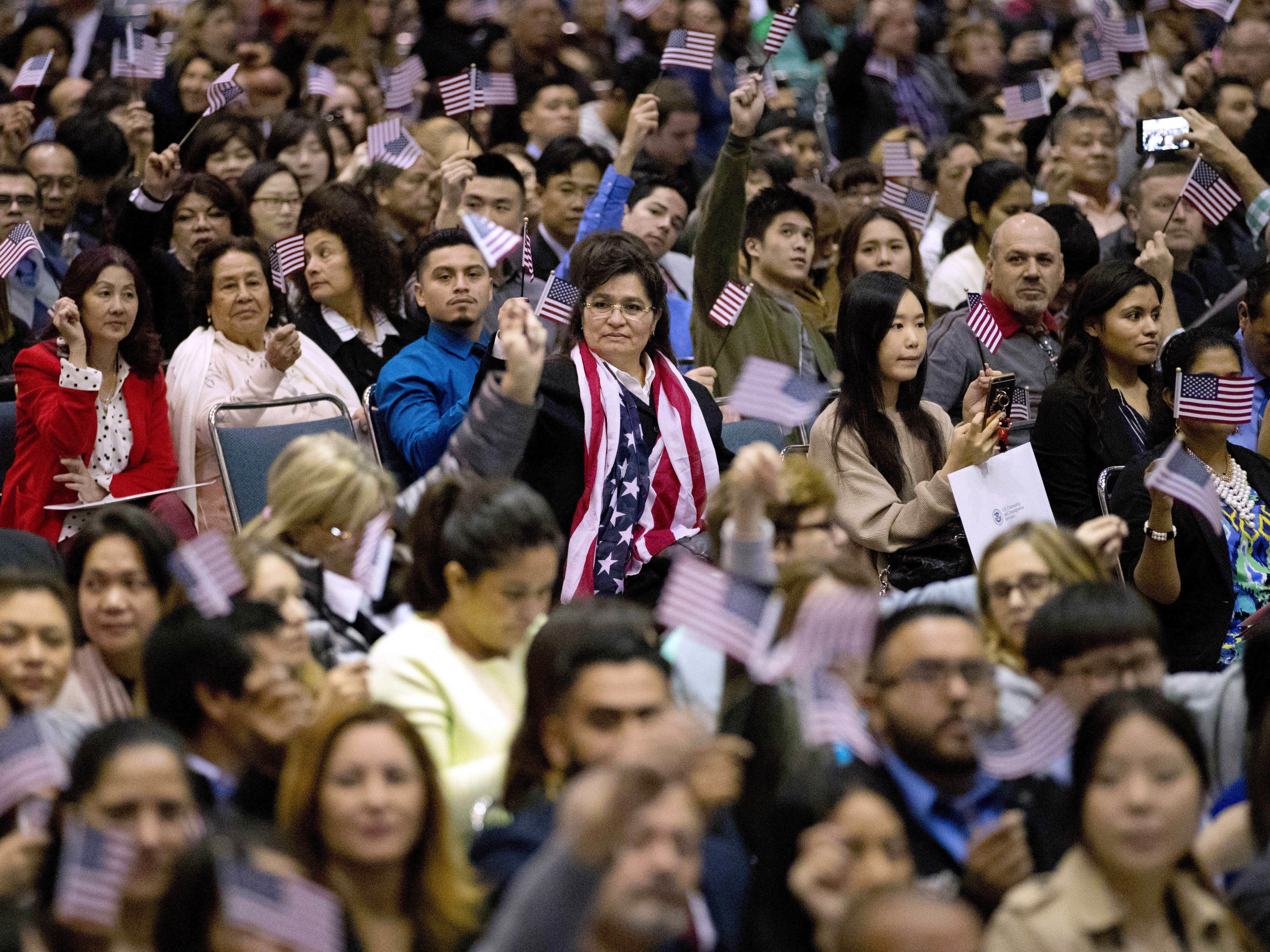 People wave U S  flags during a 2017 naturalization ceremony