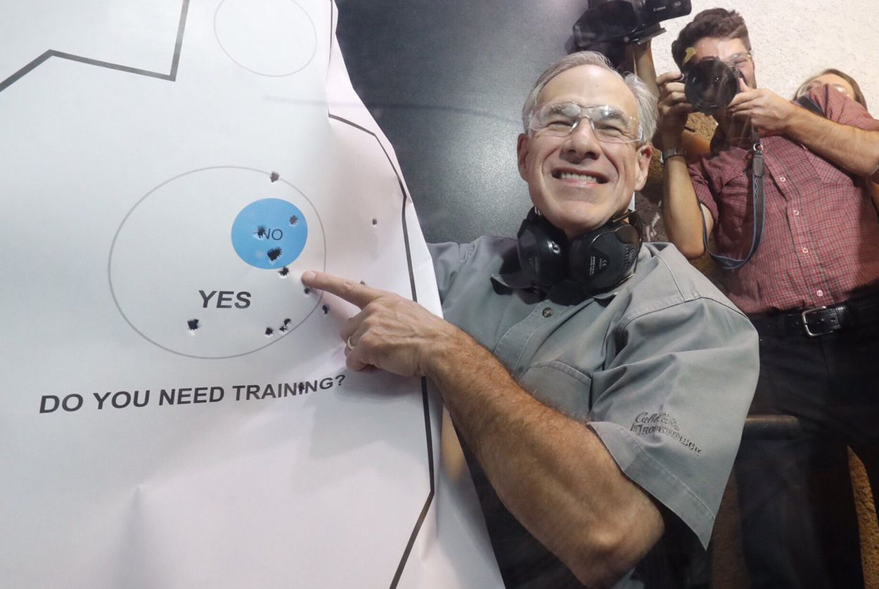 Gov. Abbott admires his practice target after signing Senate Bill 16, which reduces the first-time fee for a license to carry handguns, on May 26, 2017.