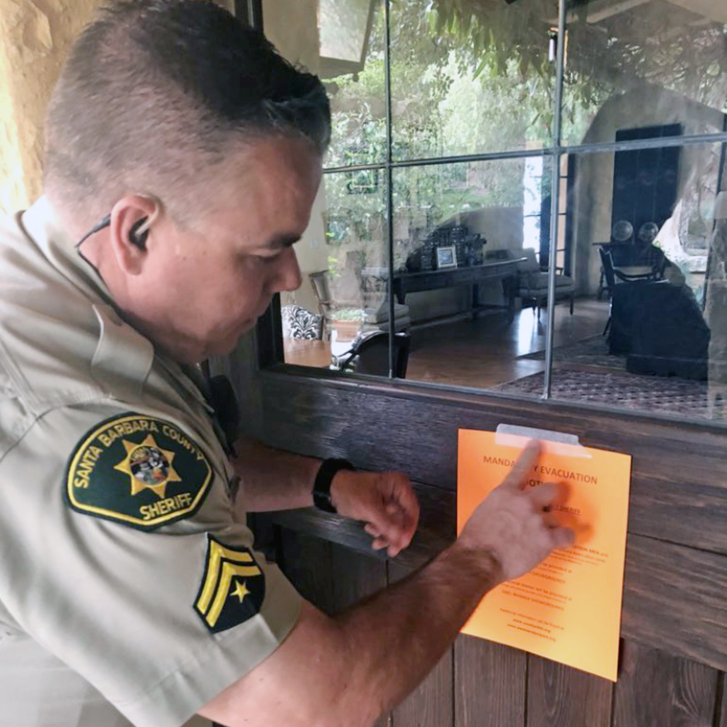 Santa Barbara County Sheriff's Deputy Mike Harris posts a notice on a home near Carpinteria, Calif., advising of the mandatory evacuation notice due to forecast rain and possible debris flow due to the recent Thomas Fire, on  Thursday.