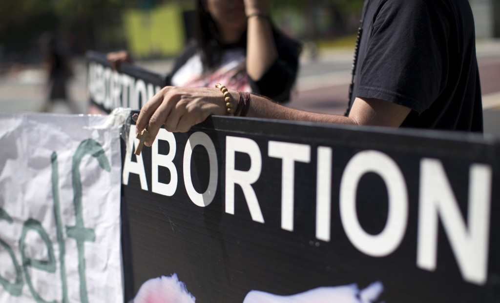 An activist holds a rosary while ralling against abortion outside City Hall in Los Angeles, California September 29, 2015. U.S. Congressional Republicans on Tuesday challenged Planned Parenthood's eligibility for federal funds, while the health organization's president said defunding it would restrict women's access to care and disproportionately hurt low-income patients.