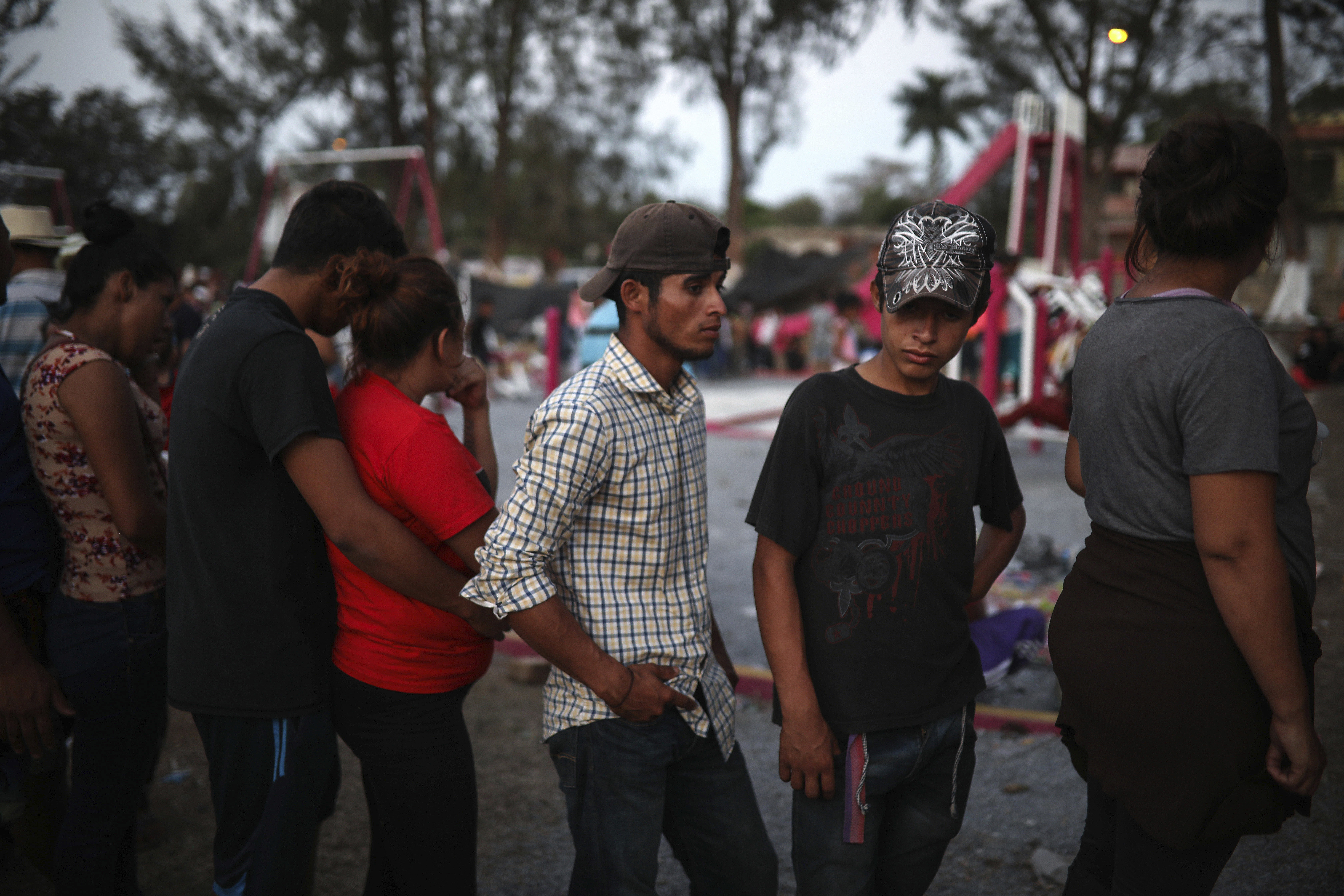 Central American migrants stand in line to start their documentation with a Mexican immigration official during the Migrant Stations of the Cross caravan as the group makes a stop at a sports center in Matias Romero, Oaxaca state, Mexico, late Monday, April 2, 2018. The annual caravans have been held in southern Mexico for years as an Easter-season protest against the kidnappings, extortion, beatings and killings suffered by many Central American migrants as they cross Mexico. (AP Photo/Felix Marquez)