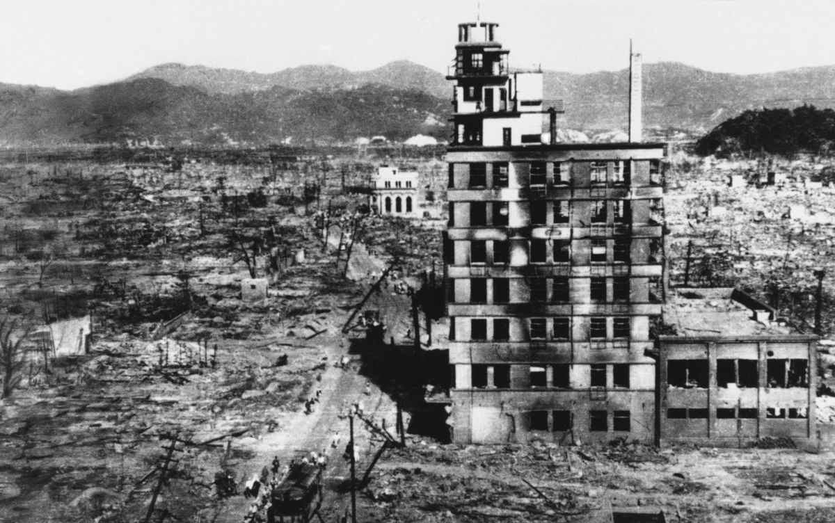 In this Aug. 8, 1945 file photo, survivors walk past one of the few buildings still standing two days after an atomic bomb was dropped on Hiroshima, Japan on August 6, 1945. The Los Alamos Historical Museum recently announced it won't be hosting a traveling exhibit organized by the Hiroshima Peace Memorial Museum and Nagasaki Atomic Bomb Museum until all parties can work out their differences over the theme.