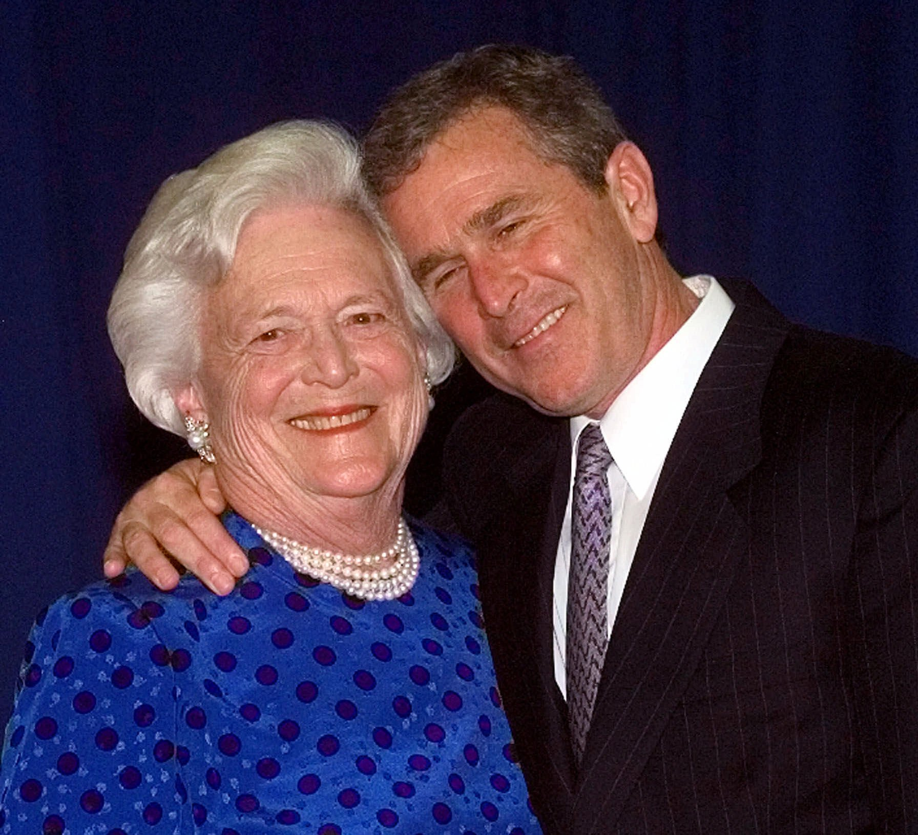 The then Texas Gov. George W. Bush, right, gives his mother, Barbara Bush , a hug after taking a family photo Thursday, June 10, 1999 in Houston.