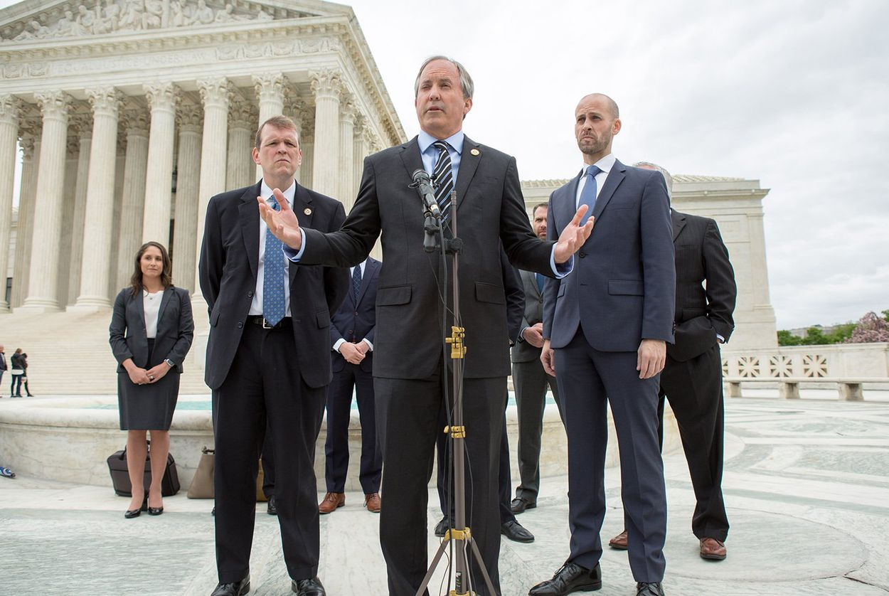 Texas Attorney General Ken Paxton, center, speaks on the steps of the U.S. Supreme Court with his team, including Texas Solicitor General Scott Keller, right, after arguments in Abbott v. Perez, a case over Texas' congressional and state House maps on April 24, 2018.