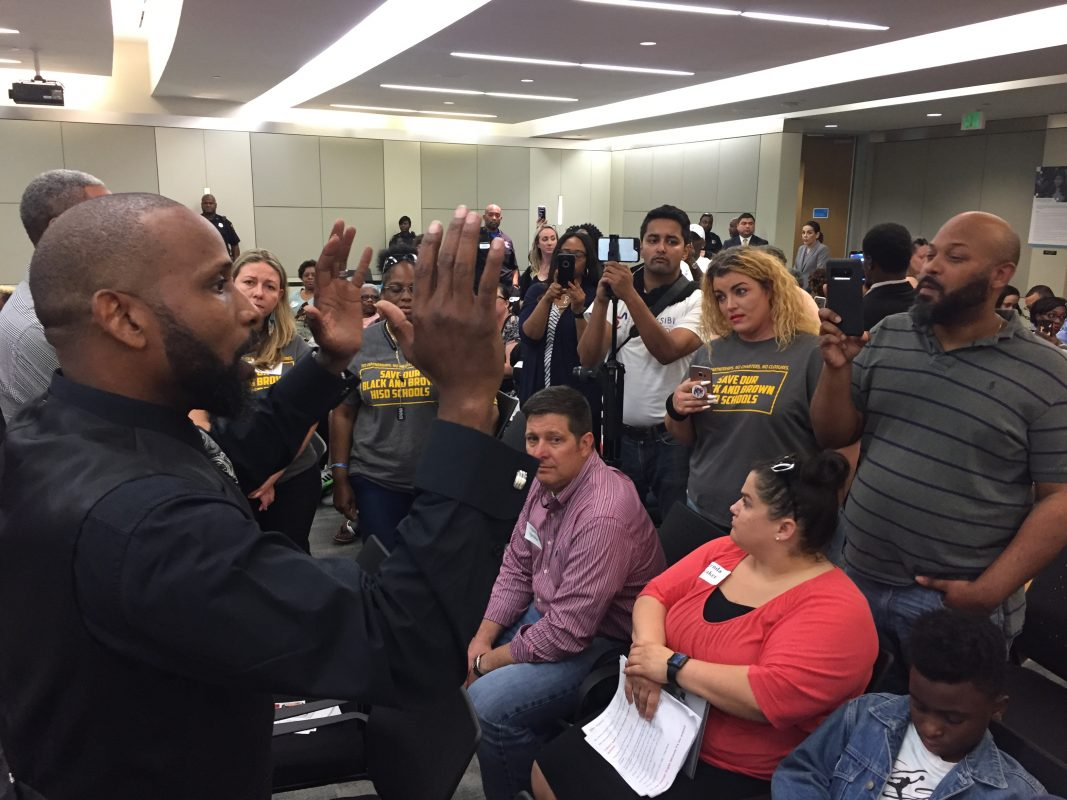 Parent and activist Travis McGee addressed a crowd of people at the HISD meeting while the board was in closed session and before a scuffle erupted with police officers.