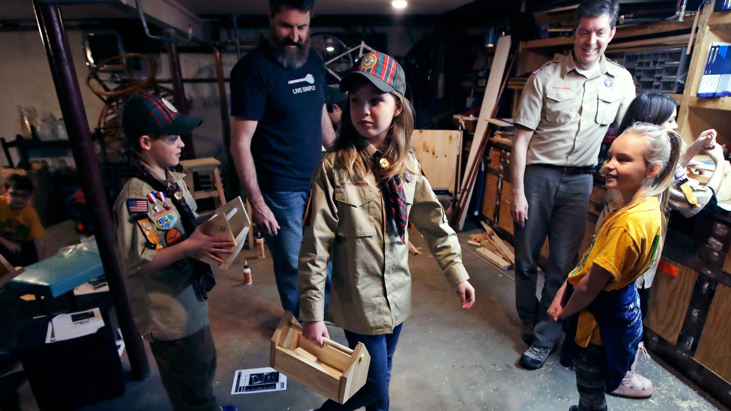 Tatum Weir (center) carries a tool box she built as her twin brother, Ian (left), follows after a Cub Scout meeting in Madbury, N.H., on March 1. For more than a century, the Boy Scouts of America's flagship program for older boys has been known as the Boy Scouts. With girls soon entering the ranks, the name will change to