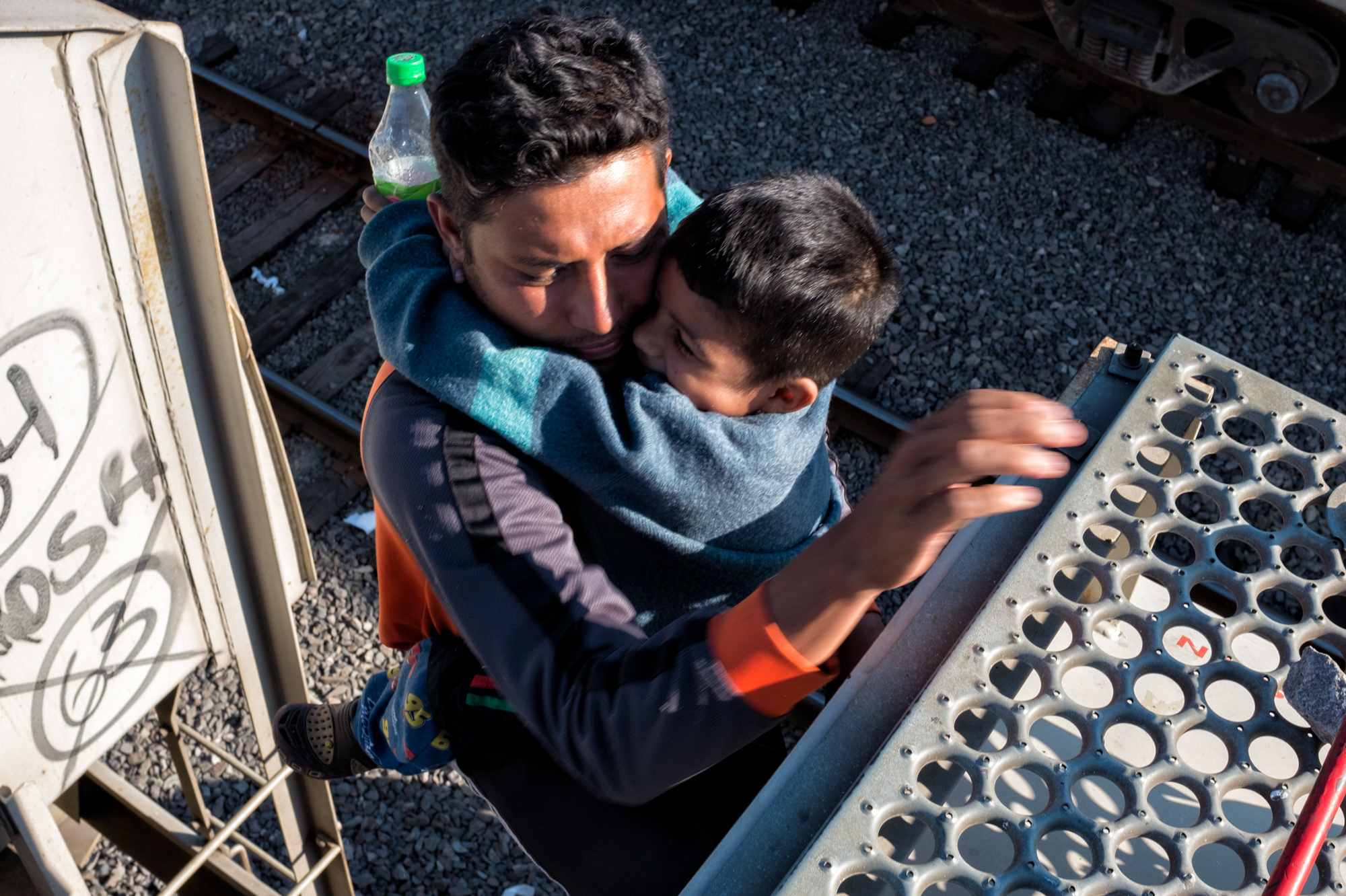 José gets off La Bestia with his son Andrée while the train stops on its way to Tijuana, Mexico, Oct. 22, 2017.